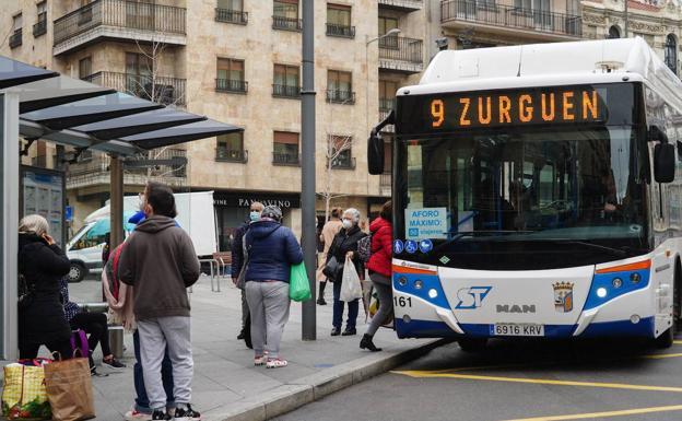 Varios usuarios en una parada del autobùs en el centro de Salamanca.
