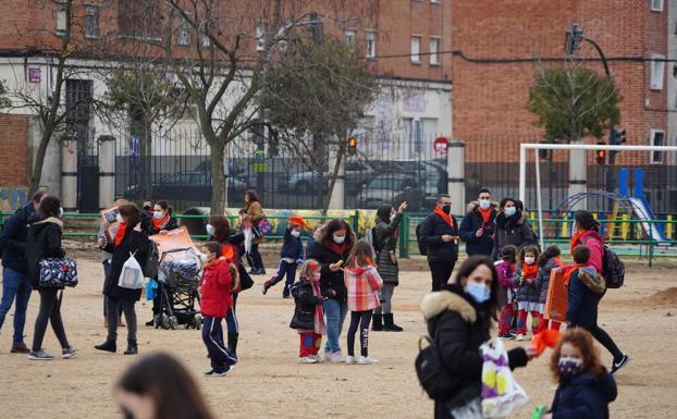 Alumnos y padres en el patio de un colegio.